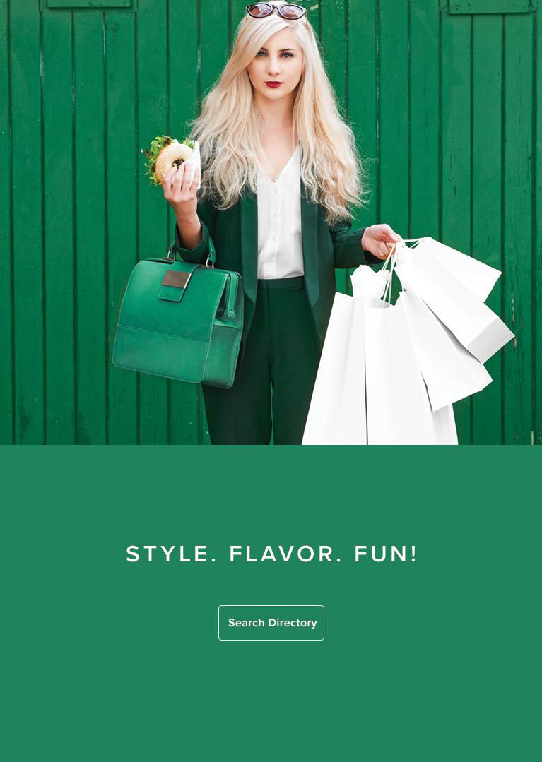 Blonde woman standing in front of a green wall holding shopping bags and a bagel sandwich.
